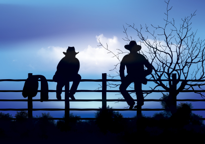 Two cowboys sitting on fence